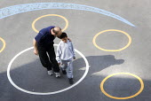 A teacher talking to a child in the playground, Hillcrest Primary School, Bristol. - Paul Box - 29-04-2009