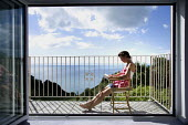 A woman relaxing on the balcony of a holiday home with a sea view, Devon. - Paul Box - 2000s,2007,apartment,apartments,balconies,balcony,bathing,book,books,chair,chairs,communicating,communication,country,countryside,deckchair,deckchairs,FEMALE,holiday,holiday maker,holiday makers,holid