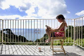 A woman relaxing on the balcony of a holiday home with a sea view, Devon. - Paul Box - 2000s,2007,apartment,apartments,balconies,balcony,bathing,book,books,chair,chairs,communicating,communication,country,countryside,deckchair,deckchairs,drink,drinking,drinks,FEMALE,holiday,holiday make