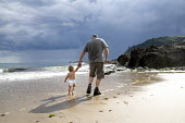 A father and son walking on a beach, in Devon. - Paul Box - 2000s,2009,and,babies,baby,beach,beaches,boy,boys,child,CHILDHOOD,children,COAST,coastal,coasts,country,countryside,DAD,DADDIES,DADDY,DADS,diaper,diapers,EARLY YEARS,families,FAMILY,father,FATHERHOOD,