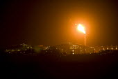 A flare stack at Milford Haven Liquid Natural Gas (LNG) Terminal, in Pembrokeshire. - Paul Box - (LNG),2000s,2009,capitalism,capitalist,chimney,CHIMNEYS,EBF Economy,energy,eni environmental issues,fire,fires,flame,flames,flare,flares,fossil,fuel,fuels,gas,Hook,Industries,industry,infrastructure,i