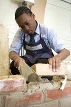 Building a wall using a trowel and mortar, Bristol City Academy, Bristol. - Paul Box - ,2000s,2008,academies,Academy,adolescence,adolescent,adolescents,BAME,BAMEs,Black,BME,bmes,boy,boys,brick,bricklayer,bricklayers,bricklaying,bricks,Building,BUILDINGS,by hand,child,CHILDHOOD,children,