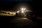 A hay bailer works late in the evening and into the night .Pembrokeshire, Wales. - Paul Box - 2000s,2009,agricultural,agriculture,at,bails,bale,baler,balers,bales,capitalism,capitalist,combine,crop,crops,cut,driver,drivers,driving,EBF,Economic,Economy,employee,employees,Employment,farm,Farm Wo