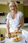 An elderly woman eating fruit for breakfast. - Paul Box - ,2000s,2009,adult,adults,age,ageing population,banana,bananas,breakfast,breakfasts,c,cities,city,diabetes,diabetic,diabetics,diet,diets,eating,elderly,EMOTION,EMOTIONAL,EMOTIONS,FEMALE,food,FOODS,frui