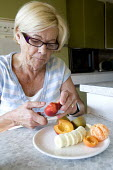 An elderly woman eating fruit for breakfast. - Paul Box - 2000s,2009,adult,adults,age,ageing population,banana,bananas,breakfast,breakfasts,c,cities,city,cut,cuts,cutting,cuttings,diabetes,diabetic,diabetics,diet,diets,eating,elderly,EMOTION,EMOTIONAL,EMOTIO