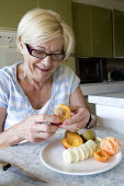 An elderly woman eating fruit for breakfast. - Paul Box - 2000s,2009,adult,adults,age,ageing population,banana,bananas,breakfast,breakfasts,c,cities,city,diabetes,diabetic,diabetics,diet,diets,eating,elderly,EMOTION,EMOTIONAL,EMOTIONS,FEMALE,food,FOODS,fruit