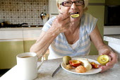 An elderly woman eating fruit for breakfast. - Paul Box - 2000s,2009,adult,adults,age,ageing population,banana,bananas,breakfast,breakfasts,c,cities,city,cup of,diabetes,diabetic,diabetics,diet,diets,eating,elderly,EMOTION,EMOTIONAL,EMOTIONS,FEMALE,food,FOOD
