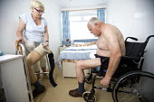 A wife helps her disabled husband get dressed. The man has had his leg amputated due to poor blood circulation. - Paul Box - 2000s,2009,adult,adults,age,ageing population,amputee,amputees,at,bed,bedroom,bedrooms,beds,blood,bound,care,carer,carers,caring,cities,city,couple,couples,Diabetes,diabetic,diabetics,Diabeties,disabi