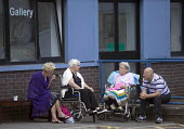 Patients sit outside a ward, Royal Victoria hospital, Edinburgh. - Paul Box - ,2010s,2014,age,ageing population,bound,care,CIGARETTE,cigarettes,communicating,communication,conversation,conversations,dialogue,disabilities,DISABILITY,disable,disabled,disablement,discourse,discuss