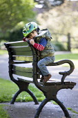 A toddler climbing on a bench. Bristol - Paul Box - 2010s,2014,andrews,bench,boy,boys,child,CHILDHOOD,children,cities,city,climbing,EARLY YEARS,emotion,emotional,emotions,helmet,HELMETS,juvenile,juveniles,kid,kids,Leisure,LFL,LIFE,male,outdoors,park,pa