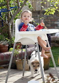 A toddler eating his lunch in a highchair at home in the garden. Bristol - Paul Box - 03-05-2014