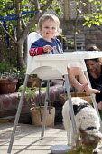 A toddler eating his lunch in a highchair at home in the garden. Bristol - Paul Box - 2010s,2014,animal,animals,boy,boys,BREAK,canine,chair,child,CHILDHOOD,children,cities,city,DINNER,dinners,DINNERTIME,dog,dogs,EARLY YEARS,eat,eating,food,FOODS,garden,GARDENS,high,highchair,home,juven