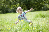 A toddler enjoying the hot weather near Bath. - Paul Box - 2010s,2014,boy,boys,BUTTERCUP,buttercups,child,CHILDHOOD,children,country,countryside,EARLY YEARS,enjoying,ENJOYMENT,field,FLOWER,flowering,flowers,grass,infancy,infant,infants,juvenile,juveniles,kid,