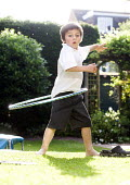 A boy plays with a hula hoop, Stratford Upon Avon - Paul Box - 2010s,2014,boy,boys,child,CHILDHOOD,children,EARLY YEARS,garden,gardens,home,homes,in,juvenile,juveniles,kid,kids,Leisure,LFL,LIFE,male,people,play,playing,RECREATION,RECREATIONAL,School Uniform,toddl