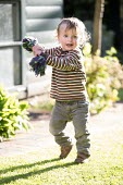 A toddler plays in a garden, Stratford Upon Avon. - Paul Box - 2010s,2014,animal,animals,boy,boys,child,CHILDHOOD,children,dog,DOGS,EARLY YEARS,fly,flying,funny,garden,gardens,Humor,HUMOROUS,HUMOUR,in,infancy,infant,infants,insect,insects,joking,juvenile,juvenile