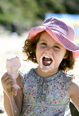 A young girl eating ice cream at Freshwater West beach, Pembrokeshire. - Paul Box - 2000s,2007,beach,BEACHES,boy,boys,child,CHILDHOOD,children,COAST,coastal,coasts,confectionery,eat,eating,female,females,food,FOODS,girl,girls,hat,hats,holiday,holiday maker,holiday makers,holidaymaker