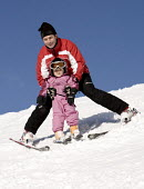 A father teaching his daughter to ski, Austria. - Paul Box - 31-12-2006
