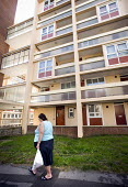 A woman walks with her bag of shopping past a block of flats. Redcliff Bristol - Paul Box - 11-09-2009