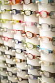A rack of multicoloured pairs of glasses at a home and living show near Cheltenham. - Paul Box - 2000s,2007,bought,buy,buyer,buyers,buying,COLOR,colorful,colorfull,colors,colour,colourful,colours,commodities,commodity,consumer,consumers,customer,customers,display,displays,EBF,Economic,Economy,eye