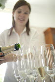 A waitress serving champagne at a PR event, Bristol. - Paul Box - 2000s,2005,bottle,bottles,CELEBRATE,CELEBRATING,celebration,celebrations,champagne,CHAMPAIGN,cities,city,employee,employees,Employment,FEMALE,flute,flutes,glass,glasses,Hospitality,job,jobs,LAB,LBR,LF