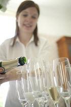 A waitress serving champagne at a PR event, Bristol. - Paul Box - 18-06-2005