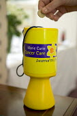 Giving, a Marie Curie Cancer Care donations tin. - Paul Box - 2000s,2005,box,boxes,cancer,CANCERS,charitable,charities,charity,collect,collecting,collection,donated,donation,donations,give,giving,help,helping,HELPS,money,PEOPLE,Social Issues,soi,UK