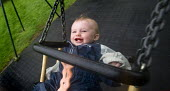 A child on a swing, Pembrokeshire. - Paul Box - 2000s,2009,babies,baby,boy,boys,child,CHILDHOOD,children,EARLY YEARS,EMOTION,EMOTIONAL,EMOTIONS,face,faces,families,FAMILY,funny,happiness,happy,Humor,HUMOROUS,HUMOUR,infancy,infant,infants,joking,juv