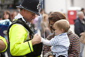 A policeman talking to a baby at the Bristol Harbour Festival. - Paul Box - 2000s,2009,adult,adults,babies,baby,boy,boys,Bristol,child,CHILDHOOD,children,cities,city,CLJ,communicating,communication,conversation,dialogue,EARLY YEARS,EMOTION,EMOTIONAL,EMOTIONS,employee,employee