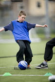 Pupils playing football at Bristol City Academy. - Paul Box - 2000s,2009,adolescence,adolescent,adolescents,ball,balls,boy,boys,child,CHILDHOOD,children,cities,city,Ed.,edu,educate,educating,education,educational,exercise,exercises,exercising,football,game,games
