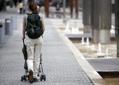 A mother and child in a pushchair. - Paul Box - 2000s,2009,adult,adults,babies,baby,child,CHILDHOOD,children,cities,city,EARLY YEARS,families,FAMILY,FEMALE,infancy,infant,infants,juvenile,juveniles,kid,kids,MATURE,mother,MOTHERHOOD,MOTHERING,mother