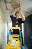 Selwood Housing maintenance man replacing a bulb from his step ladder. Selwood manage and maintain quality affordable housing and provide support services for people in housing need - Paul Box - 03-08-2009