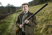 A shooting enthusiast with his double barreled shotgun, Exmoor. - Paul Box - 12,2000s,2009,Barbour Jacket,blood sport,bore,country,countryside,enthusiasm,enthusiastic,gun,guns,hobbies,hobby,hobbyist,hunt,hunter,hunters,hunting,hunts,Leisure,LFL,LIFE,male,man,men,outdoors,outsi