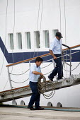 Seafarers putting a passenger gangway in place as a cruise ship docks at Pembroke dock, Wales. - Paul Box - 05-08-2011