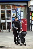An elderly man shopping Southmead, Bristol. - Paul Box - 2010s,2011,age,ageing population,bought,buy,buyer,buyers,buying,commodities,commodity,consumer,consumers,corner shop,customer,customers,EBF Economy,elderly,goods,LFL,LIFE,man men,old,pavement,pedestri