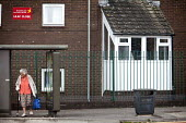 An elderly woman waiting for a bus outside her Brunelcare residential care home, Southmead, Bristol. - Paul Box - 2010s,2011,adult,adults,age,ageing population,bus,bus service,Bus Stop,BUSES,cities,city,elderly,FEMALE,home,homes,housing,MATURE,OAP,OAPS,old,outside,pavement,pedestrian,pedestrians,pensioner,pension