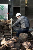 Builder laying a stone wall on a barn conversion. - Paul Box - 2010,2010s,barn,bricklayer,bricklayers,bricklaying,Brownfield Site,bubble level,builder,builders,building site,Building Worker,check,checking,checks,Construction Industry,Construction Workers,conversi