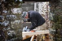 A carpenter cuts the oak A-frames for a barn conversion. - Paul Box - 2010,2010s,A-frame,A-frames,barn,Brownfield Site,builder,builders,building site,Building Worker,carpenter,circular,Construction Industry,Construction Workers,conversion,cut,cuts,cutting,developer,deve