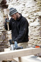 A carpenter cuts the oak A-frames for a barn conversion. - Paul Box - 2010,2010s,A-frame,A-frames,barn,Brownfield Site,builder,builders,building site,Building Worker,carpenter,circular,Construction Industry,Construction Workers,conversion,cuts,developer,developers,devel