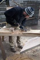 A carpenter cuts the oak A-frames for a barn conversion. - Paul Box - 2010,2010s,A-frame,A-frames,barn,Brownfield Site,builder,builders,building site,Building Worker,carpenter,Chisel,Chisels,circular,Construction Industry,Construction Workers,conversion,cuts,developer,d