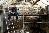 Builder takes a break on a barn conversion. - Paul Box - 2010,2010s,barn,break,break time,Brownfield Site,builder,builders,building site,Building Worker,Construction Industry,Construction Workers,conversion,danger,dangerous,developer,developers,development,