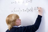 Pupil wrting an equation on the whiteboard, Bristol City Academy. - Paul Box - 27-04-2010