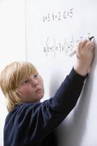 Pupil wrting an equation on the whiteboard, Bristol City Academy. - Paul Box - 2010,2010s,adolescence,adolescent,adolescents,algebra,arithmetic,boy,boys,child,CHILDHOOD,children,cities,city,class,classroom,CLASSROOMS,edu,educate,educating,education,educational,juvenile,juveniles