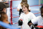 Students try boxing at Sports Week at Bristol City Academy. - Paul Box - 2010,2010s,BAME,BAMEs,black,BME,bmes,boxer,boxers,boxing,Boxing Gloves,Boxing Match,boy,boys,child,CHILDHOOD,children,cities,city,class,combat,court,cultural,diversity,edu,educate,educating,education,
