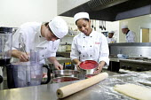 Students learning to become chefs at Bristol City Academy. - Paul Box - 2010,2010s,adolescence,adolescent,adolescents,BAME,BAMEs,black,BME,bmes,boy,boys,cake,cakes,caterer,caterers,catering,chef,chefs,child,CHILDHOOD,children,cities,city,class,classroom,CLASSROOMS,cook,CO