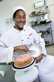 Students learning to become chefs at Bristol City Academy. - Paul Box - 2010,2010s,adolescence,adolescent,adolescents,apron,aprons,bakery,BAME,BAMEs,Black,BME,bmes,cake,cakes,caterer,caterers,catering,chef,chefs,child,CHILDHOOD,children,cities,city,class,classroom,CLASSRO