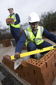 A pupil learns how to build a brick wall in a ITC design technology lesson, Bristol City Academy. - Paul Box - 2010,2010s,adolescence,adolescent,adolescents,BAME,BAMEs,black,BME,bmes,boy,boys,brick,bricklaying,bricks,bubble level,child,CHILDHOOD,children,cities,city,class,Construction Workers,cultural,design,D