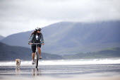 A cyclist riding with her dog on Brandon bay, Kerry, Ireland - Paul Box - 15-08-2010
