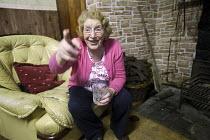 An elderly woman at home. Kerry, Ireland - Paul Box - 2010,2010s,age,ageing population,drink,drinking,elderly,EMOTION,EMOTIONAL,EMOTIONS,eu,Europe,european,europeans,eurozone,FEMALE,funny,having fun,home,homes,Humor,HUMOROUS,HUMOUR,Ireland,Irish,JOKE,JOK