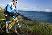 A mountain biker cycling on the coastal path. - Paul Box - 17-11-2009