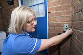 Community nurse on her rounds ringing the doorbell. Bristol - Paul Box - 2010,2010s,care,cities,city,communities,Community,community nurse,district,door,doorbell,doors,EARNINGS,employee,employees,Employment,EQUALITY,FEMALE,hea,health,HEALTH SERVICES,Health Visitor,Health V